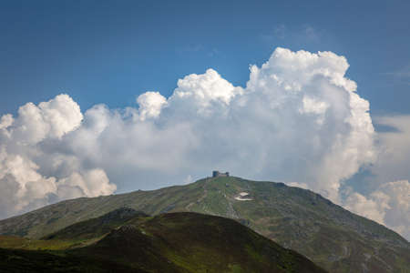 Mountain peak Popivan (Pip Ivan, Pop Iwan) with abandoned old observatory building on top in rainy weather, panoramic view. Chornohora range, Carpathian Mountains, Ukraine