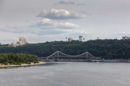 View of the Dnipro river embankment and the pedestrian bridge in Kyiv, Ukraine Stock Photo