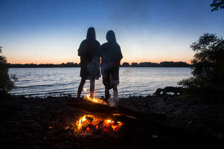 Fire and two pretty girls meeting the dawn on the river. Camping on the magical Dnieper (Dnipro)