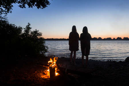 The silhouettes couple of girls near the campfire by the river greeting the sunrise. Travel outdoor concept camping morning view
