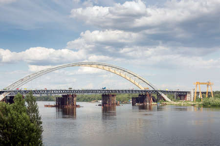 Construction of a new arch bridge across the Dnipro (Dnieper) River, Kyiv, Ukraine. Large infrastructure facility on the water