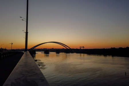 Sunset view of the new arch bridge construction across the Dnipro (Dnieper) River, Kyiv, Ukraine. Large infrastructure facility on the water