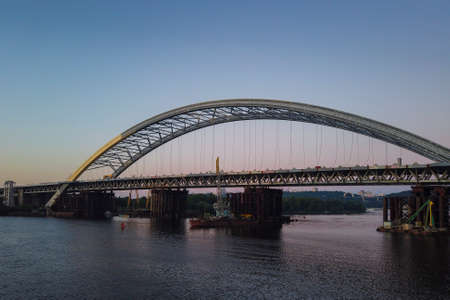 Construction of a new arch bridge across the Dnipro (Dnieper) River, Kyiv, Ukraine. Sunset view of the large infrastructure facility on the water