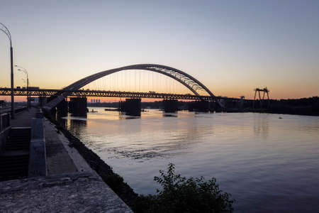 Evening view of the new arch bridge construction across the Dnipro (Dnieper) River, Kyiv, Ukraine. Large infrastructure facility on the water Stock Photo