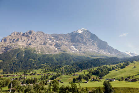 Green Swiss meadows and the North face of the Eiger mountain of the Bernese Alps, Grindelwald, Switzerland Stock Photo - 152027629
