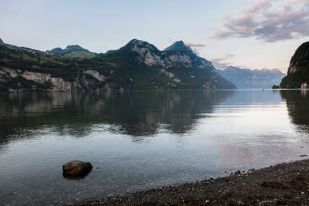 Beautiful alpine sunset view with reflections at the Lake Walensee in Swiss Alps, Switzerland Stock Photo