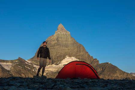Hiker near a campsite under the Swiss side of Matterhorn mountain in the evening sun, Zermatt, Switzerland Editorial