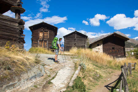 Hiker with a backpack among a Swiss mountain farm, Zermatt, Switzerland