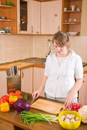 The woman cuts vegetables