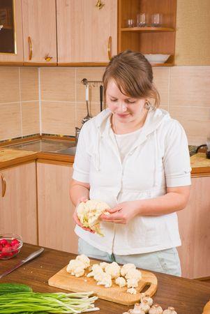 The girl divides a cauliflower