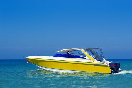 Yellow boat driving in the ocean water Stock Photo