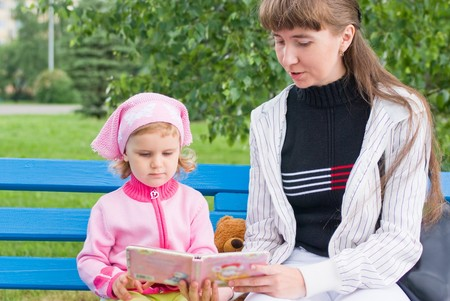 Mother and daughter reading a book on a park bench