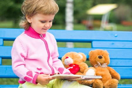 A little girl reads books to his teddy bear in the park