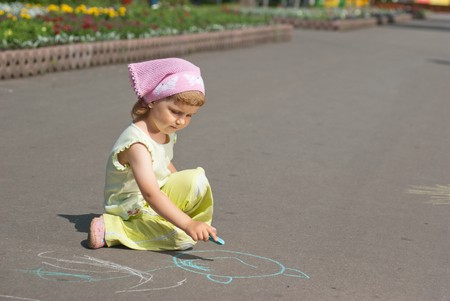 Girl drawing with crayons on the asphalt