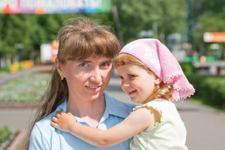 A little girl hugs her moms shoulder, smiling