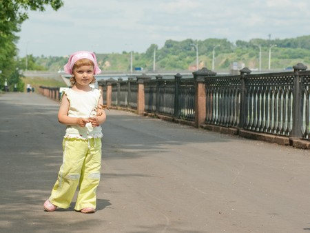 A little girl walks alone in the park on track