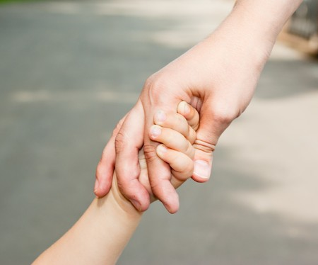 Mom keeps daughters hand, close-up on the street