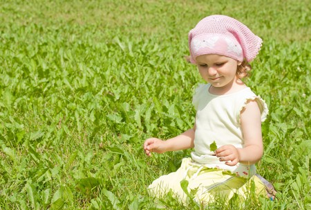 A little girl sits on a green lawn, playing with a leaflet