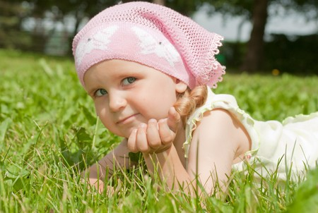 A little girl lying on the green lawn, close-up