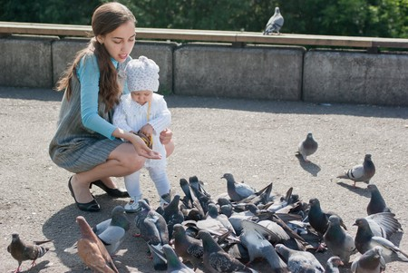 Mom and daughter feeding pigeons Stock Photo