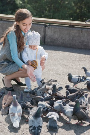 Mom and daughter feeding pigeons photo