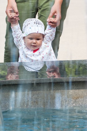 A little girl looks up at the fountain, holding his mother's arms Stock Photo - 7475478
