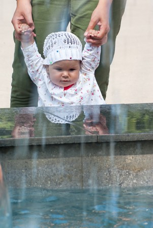A little girl looks up at the fountain, holding his mother's arms Stock Photo - 7475467