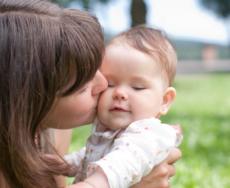Mom kisses her little daughter, played in the park Stock Photo