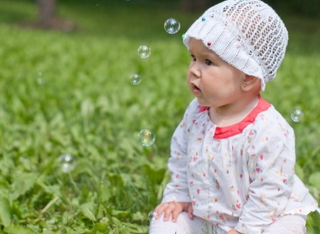 A little girl sitting on green grass in the park looking at soap bubbles Stock Photo