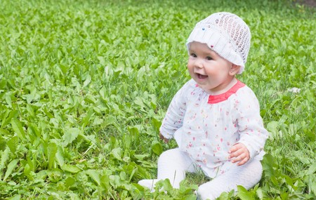 A little girl sitting on green grass in the park  Stock Photo