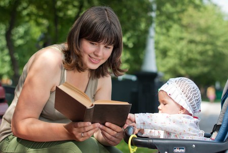 Mom reads a book of his little daughter in the park photo