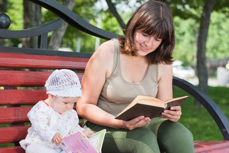 Mother and daughter reading book in the park on a bench
