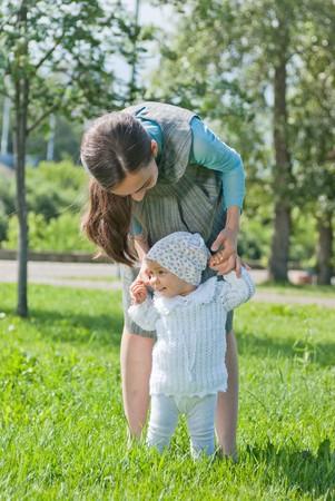 teaches: Mom teaches her little daughter to walk, hands