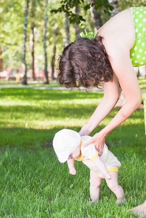 Mom teaches her baby to walk on the grass