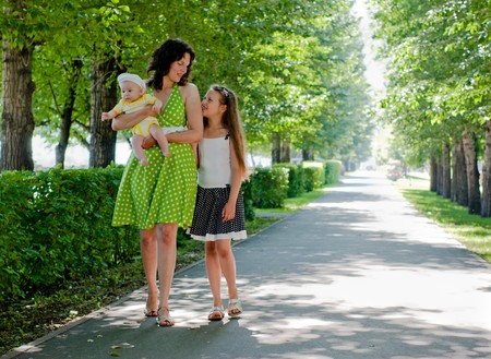 woman and two children walking down the avenue in the park photo