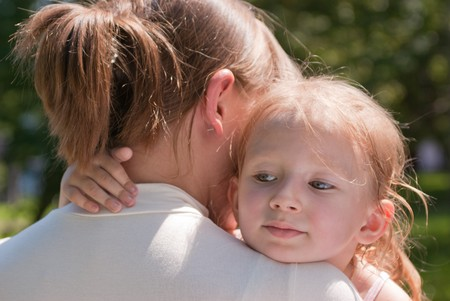 little girl hugging her mothers neck, rear view, put her head on his shoulder
