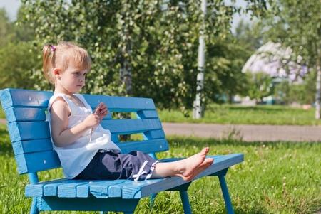 dreamy girl on a park bench Stock Photo