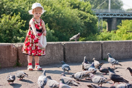 girl in a dress and a white hat feeding pigeons