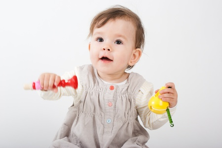 The little girl plays with wooden toys a white background
