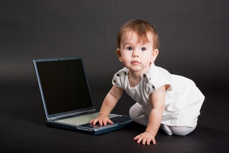 The little girl in a white dress with the laptop on a black background photo