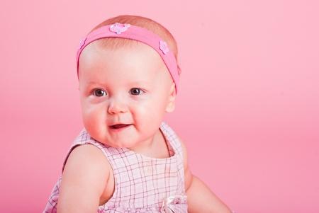 Portrait of the small beautiful joyful girl on a pink background
