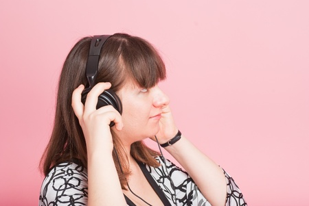 The pregnant girl listens to music in ear-phones photo
