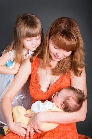 Mum with a daughter look at the newborn kid photo