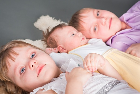 Portrait of three children on a gray background