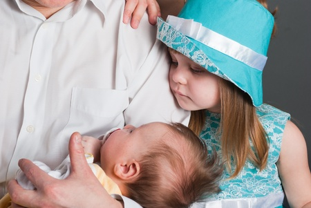 The little girl looks at the newborn kid