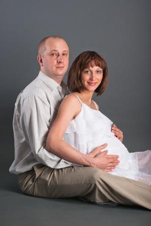 The husband embraces the pregnant wife