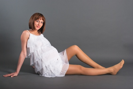 The pregnant woman on a gray background Stock Photo
