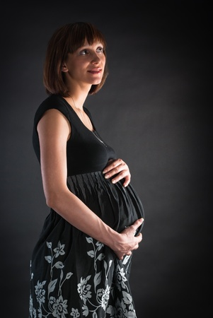The thoughtful pregnant woman holds a stomach on a gray background