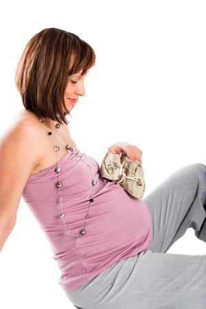 The pregnant woman looks at bootees, a white background Stock Photo - 10545349
