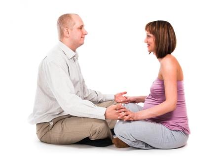 esposas: El marido y la esposa embarazada mantienen en una pose de yoga